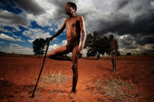 Kalahari Desert, South Africa-October 2006: Shoot with Kalahari San Bushmen in conjunction with Lion Television Productions for Discovery Atlas series. The shoot examines 2 days in the shooting schedule. The film attempts to portray aspects of traditional life for the Bushmen people. It examines a long hunt involving the 4 men and also a trance dance which is traditionally done to ensure a good hunt, certain weather etc. The dance helps to gird the Bushmen for the taxing exertion of the hunt. the 4 main protagonists were as follows: Hans Witboy, 23, he is the youngest of the 4. Buks Hendrik Kruiper, 50, he has an element of red to his loin cloth and very slitted eyes. Isak Kruiper, 48, is often the leader of the group. He wears an animal skin hat in the pictures. Abijong Kruiper, 63, is the oldest member and he stands often on one leg while waiting, resting one leg on the other. Pictures by Brent Stirton for the Discovery Channel.